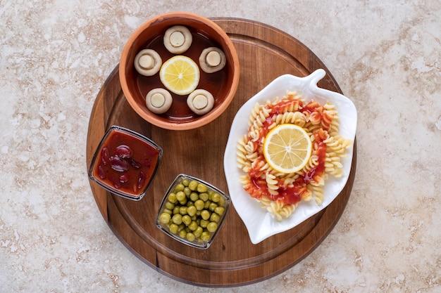 Assiette de pâtes cuites avec diverses portions de garniture sur un plateau en bois sur une surface en marbre