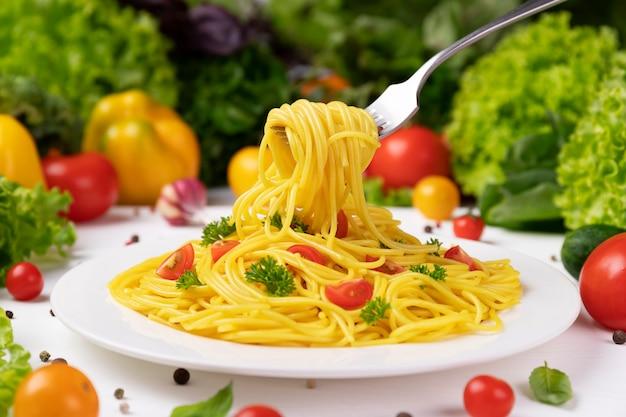 Assiette de pâtes italiennes cuites à la pipe rigate avec tomates et feuilles de basilic avec beaucoup de nourriture autour