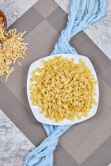 Une assiette de pâtes non cuites avec nappe bleue sur table en marbre.