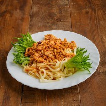 Une assiette de pâtes à la sauce bolognaise sur une table en bois. photo verticale