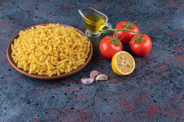 Une assiette de pâtes en spirale non cuites avec de l'huile et des tomates rouges fraîches sur un fond sombre.