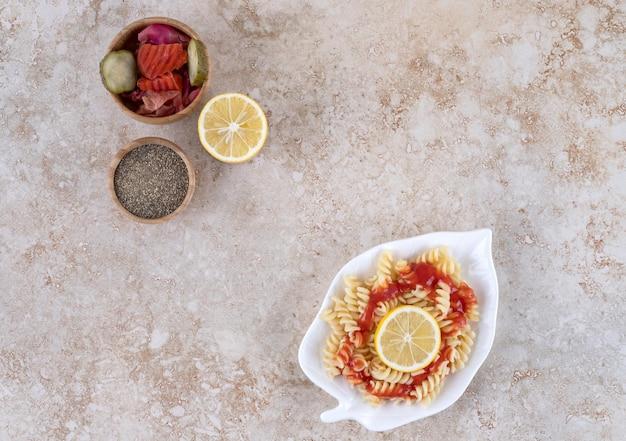 Assiette de pâtes, tranche de citron, cornichons assortis et un bol de poivre noir sur une surface en marbre