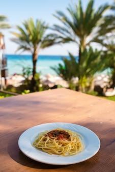 Assiette de pâtes avec vue sur la mer. le concept de détente.
