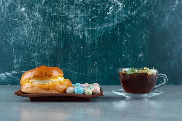 Assiette de pâtisserie et bonbons avec tasse de thé sur marbre.
