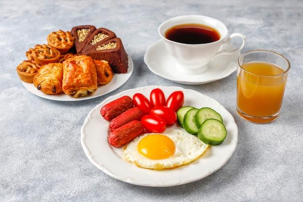 Une assiette de petit-déjeuner contenant des saucisses à cocktail, des œufs au plat, des tomates cerises, des bonbons, des fruits et un verre de jus de pêche.