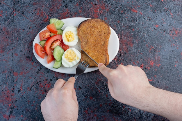 Assiette de petit déjeuner avec des tranches d'oeuf, de concombre, de tomate et de pain.