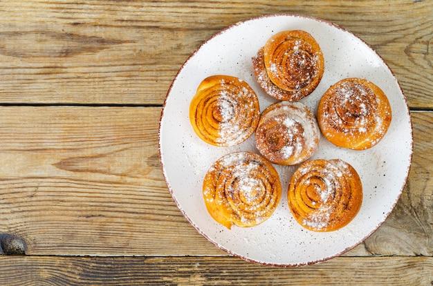 Assiette de petits pains à la cannelle maison sur table en bois