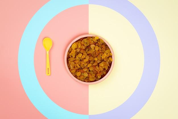Assiette en plastique rose avec raisins secs jaunes et une cuillère jaune dans un fond isolé jaune-rose.
