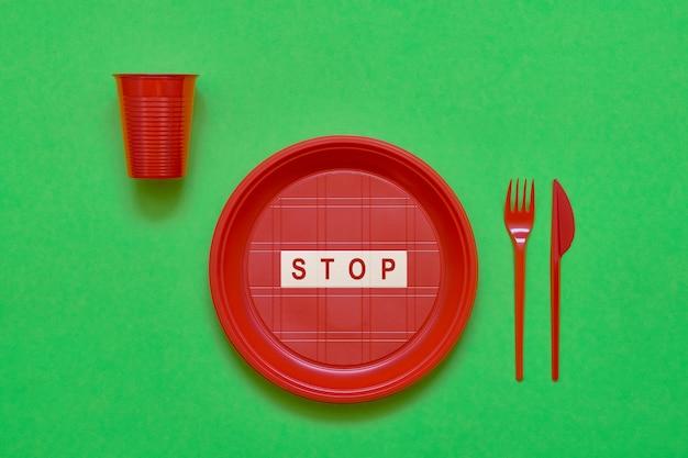 Assiette en plastique rouge jetable avec mot stop à l'intérieur, couteau rouge et fourchette sur vert. vue de dessus