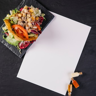 Assiette avec plat mexicain près de feuille de papier