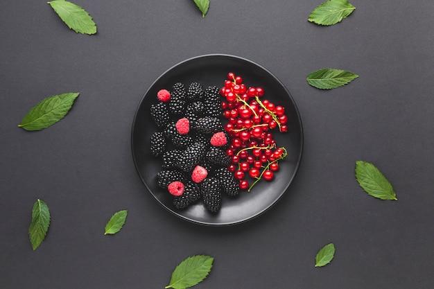 Assiette plate de baies fraîches avec des feuilles