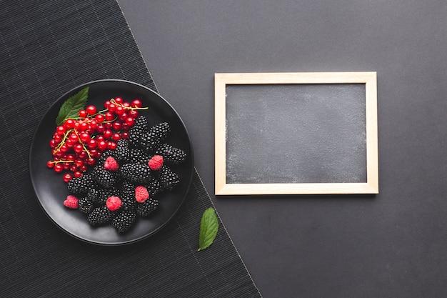 Assiette plate de baies fraîches avec tableau noir