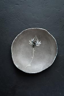 Assiette plate rustique vide d'argile grise avec belle fleur sur table en béton noir. mise au point sélective. vue de dessus. copiez l'espace.