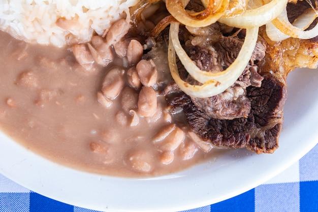 Assiette de plats brésiliens typiques - steak à l'oignon