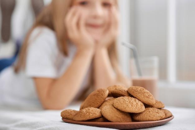 Assiette pleine de biscuits et de verre au lait au chocolat sur fond de filles.