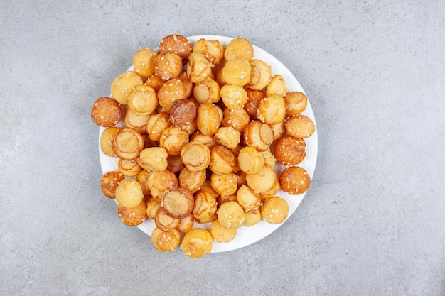 Une assiette pleine de petits cookies sur fond de marbre. photo de haute qualité