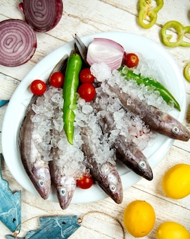 Assiette de poisson cru garni de poivre, tomate cerise et oignon rouge