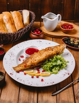 Assiette de poisson frit garnie de laitue citronnée et sauce rouge