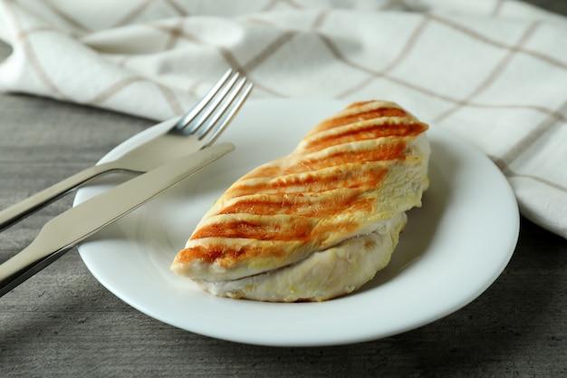 Assiette avec poitrine de poulet grillée sur table texturée grise