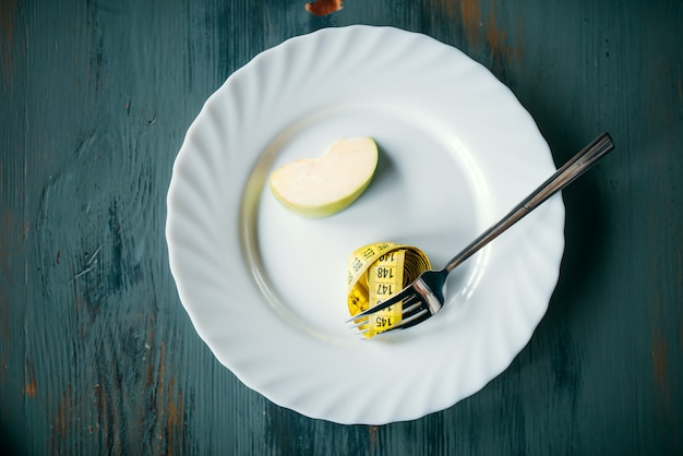Assiette avec pomme et ruban à mesurer, perte de poids