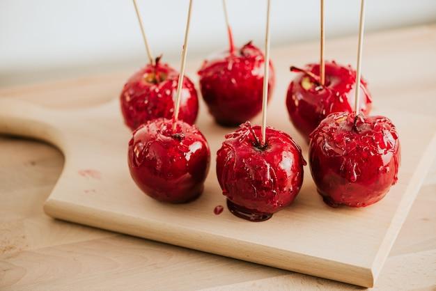 Assiette avec des pommes bonbons délicieux sur une table en bois.