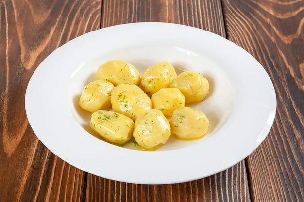 Assiette de pommes de terre bouillies sur table en bois
