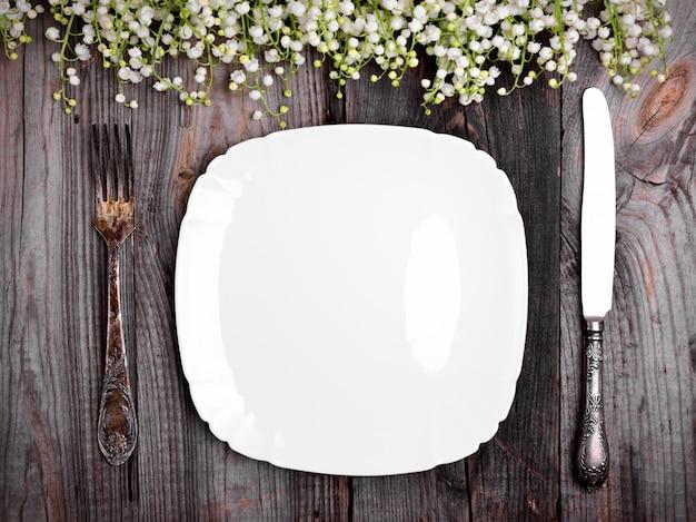 Assiette en porcelaine blanche avec couverts vintage en fer
