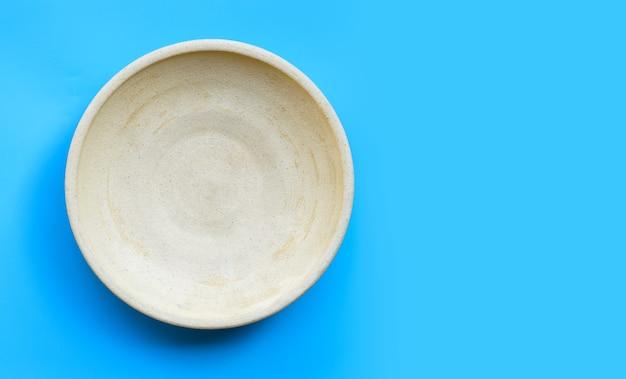 Assiette de poterie vide sur bleu isolé. copier l'espace