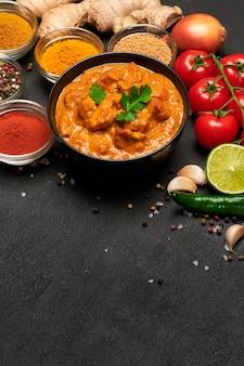 Assiette de poulet au curry traditionnel et épices sur table sombre