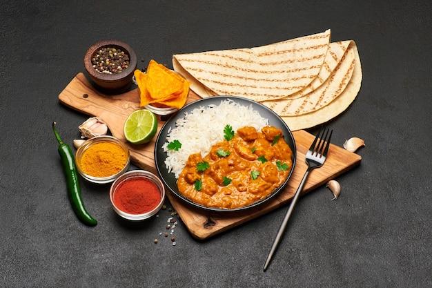 Assiette de poulet au curry traditionnel et riz sur table sombre