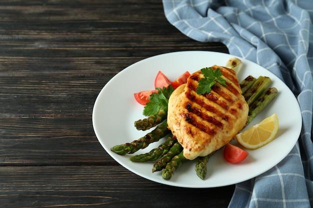 Assiette avec poulet grillé et ingrédient sur fond de bois