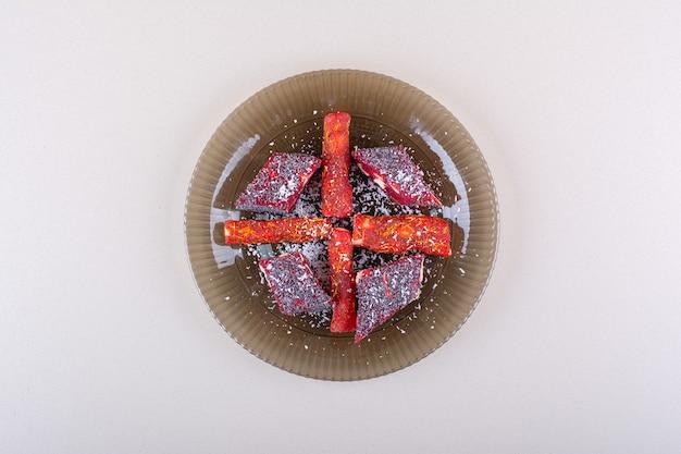 Assiette de pulpes de fruits confits placée sur fond blanc. photo de haute qualité