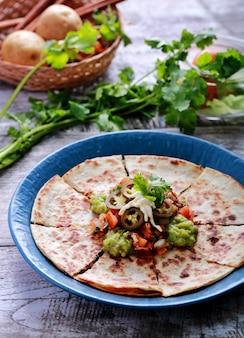 Une assiette de quesadilla servie avec salsa, guacamole et jalapenos