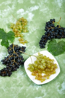 Une assiette de raisins blancs et de raisins noirs avec des feuilles sur fond vert. photo de haute qualité