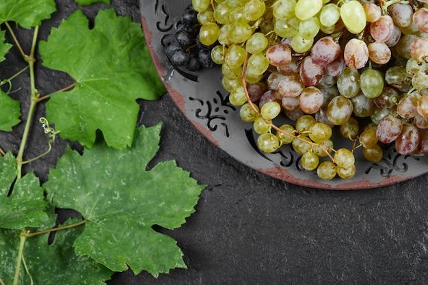 Une assiette de raisins mélangés avec des feuilles sur fond sombre. photo de haute qualité