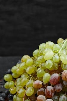 Une assiette de raisins mélangés sur fond sombre. photo de haute qualité