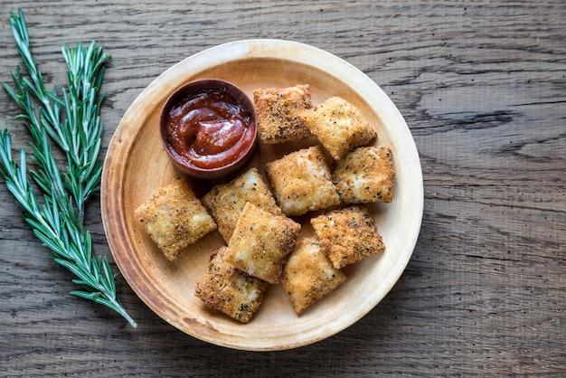 Assiette avec raviolis frits sur la planche de bois