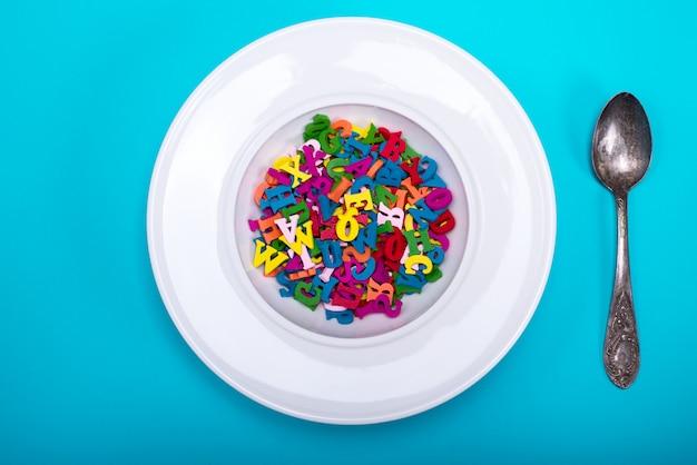 Assiette remplie de lettres en bois multicolores