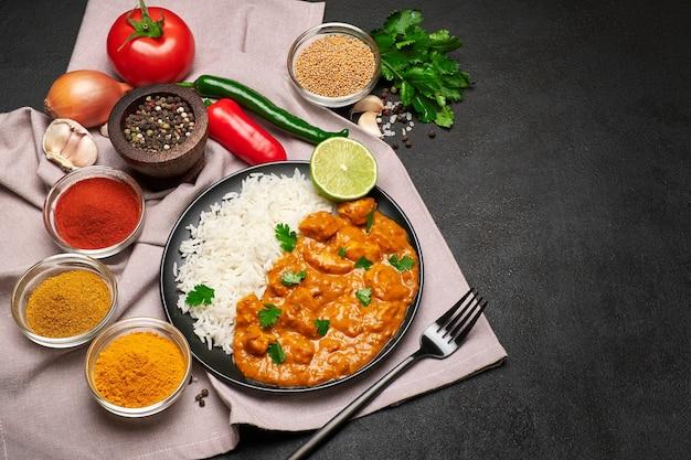 Assiette de riz au curry de poulet traditionnel et épices sur table sombre