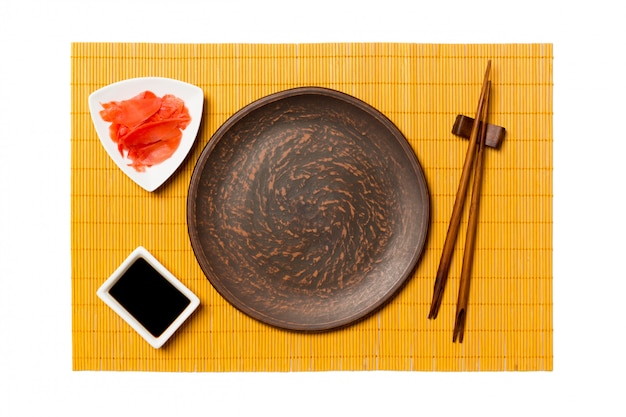 Assiette ronde brune vide avec des baguettes pour sushi, gingembre et sauce soja sur tapis en bambou jaune
