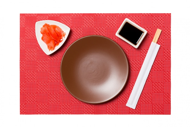 Assiette ronde brune vide avec baguettes pour sushi et sauce soja, gingembre sur sushi rouge mat