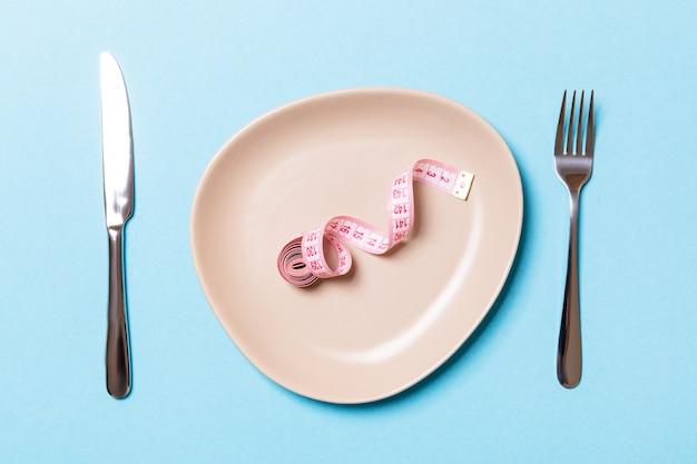 Assiette ronde avec du ruban de mesure à l'intérieur avec une fourchette et un couteau sur fond bleu
