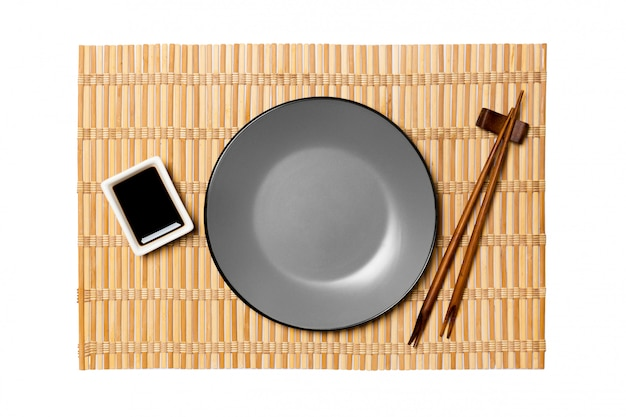 Assiette ronde grise vide avec des baguettes pour sushi et sauce soja sur tapis en bambou jaune. vue de dessus avec fond