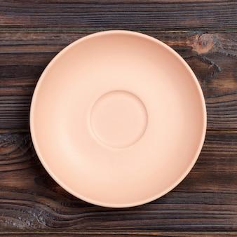 Assiette ronde rose ou corail vide sur fond de table en bois.