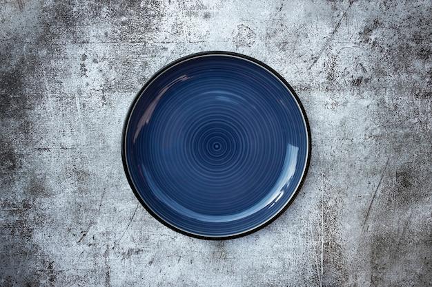 Assiette ronde vide bleu foncé placée au milieu de la table béton noir et blanc, vue de dessus
