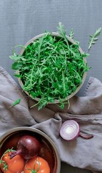 Assiette avec roquette verte fraîche, oignon et tomate sur fond gris, vue du dessus.