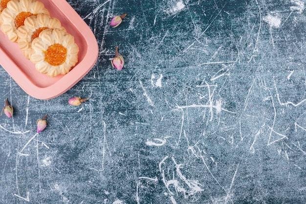 Assiette rose de biscuits à la gelée posée sur du marbre.