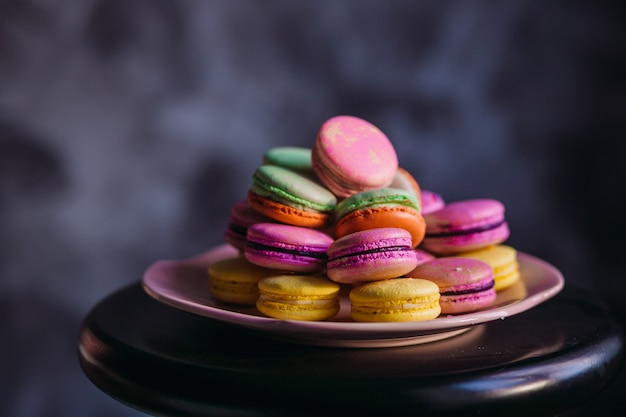Assiette rose avec de délicieux macarons colorés