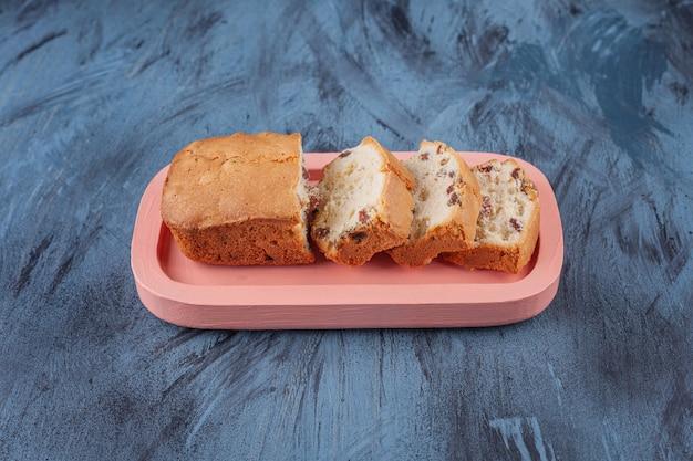 Assiette rose de gâteau aux raisins en tranches sur une surface en marbre.