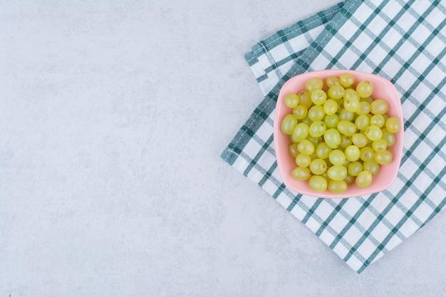 Une assiette rose pleine de délicieux raisins verts. photo de haute qualité